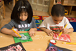 Education Preschool 4 year olds art activity boy and girl usng paint brushes, girl using right hand and boy using left hand
