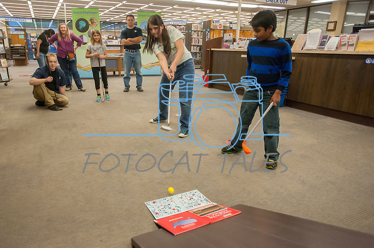 Katie Tubiello attempts a difficult ramp shot while other watch during the Mini Golf Night at the Carson City Library on May 9, 2014. Parents and children enjoyed turning the library into a mini golf course. The kids used engineering concepts to build ramps, tunnels and obstructions.<br /> (Photo by Kevin Clifford/Nevada Photo Source)