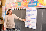 K-8 Parochial School Bronx New York Grade 4 social studies science female teacher talking to class using poster showing problems and actions leading to solutions horizontal
