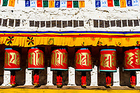 Colourful prayer wheels in Paro town. Buddhists believe that mindfully spinning a prayer wheel produces the same benefits and merits as orally reciting the number of mantras inside the prayer wheel