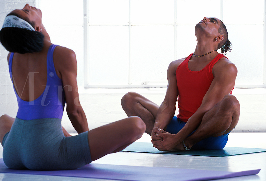Man and woman practicing yoga together,