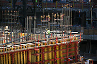 Tenth anniversary of 9/11.  Rebuilding at the World Trade Center site.  Iron worker toils atop under-construction transportation hub.  One World Trade Center is directly behind the hub.  Photo by Ari Mintz.  8/11/2011.
