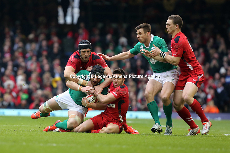 Pictured: Sean O'Brien of Ireland (2nd L) is brought down by Luke Charteris (L) and Rhys Webb (3rd L) of Wales Saturday 14 March 2015<br /> Re: RBS Six Nations, Wales v Ireland at the Millennium Stadium, Cardiff, south Wales, UK.
