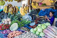 Punakha, Bhutan.  Vendor of Fruits and Vegetables Checking her Cell Phone, Lobeysa Market.