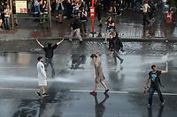 """GERMANY, Hamburg, protest rally """"WELCOME TO HELL"""" against G-20 summit in july 2017, police uses water cannon and teargas against autonomous mummed protester of the so called Black Block / DEUTSCHLAND, Hamburg, Fischmarkt, Demo Welcome to Hell gegen den G20 Gipfel in Hamburg, Polizei setzt Wasserwerfer und Traenengas gegen vermummte Linksextremisten des schwarzen Block ein, Jugendliche im Bademantel mit der Aufschrift Party Polizei"""