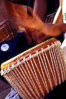 Close up of a man playing an African jimbe drum