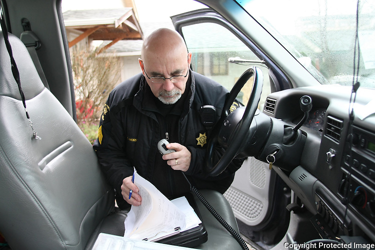 King County Animal Care and Control cruelty investigator, Sgt. David Morris, fills out paperwork after checking on a dog in Enumclaw, Wash. on December 10, 2008.  The Husky mix in Eunemclaw, WA had no water, was living admist feces everywhere, and his shelter was too small for him. (Karen Ducey/Seattle Post-Intelligencer)