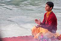 India, Rishikesh.  Young Monk Praying Evening Prayer (Aarti) at the Parmarth Niketan Ashram, on the Banks of the Ganges (Ganga).