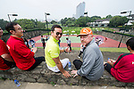 Tennis Legend Boris Becker (right, orange cap) and Mission Hills vice-chairman Tenniel Chu (left, yellow shirt) observe junior tennis players play at Mission Hills Resort on 19 March 2016, in Shenzhen, China. Photo by Lucas Schifres / Power Sport Images