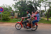 """Cambodian Ambulance"" transporting a sick child by Motorbike in the rural area of Cambodia"