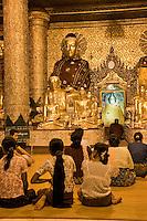 Myanmar, Burma.  Shwedagon Pagoda, Yangon, Rangoon.  Evening Lights Illuminate  Worshipers Praying in a Buddhist Shrine.