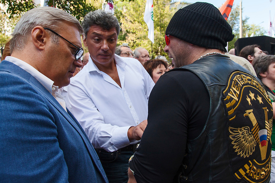 Moscow, Russia, 19/08/2012..Opposition leaders and former Russian Prime Ministers Mikhail Kasyanov and Boris Nemtsov inspect the insignia of a member of the Russian Veterans Motorcycle Club at an opposition rally. Several hundred opposition demonstrators gathered near the Russian government White House to mark the 21st anniversary of the attempted coup in 1991 by Communist hardliners that led to the eventual break-up of the Soviet Union.