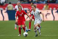 Jessie Fleming #17 of Canada moves after Emily Sonnett #2 of the United States ball with the ball