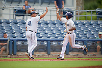 Charlotte Stone Crabs manager Jeff Smith (41) congratulates Kaleo Johnson (10) after a home run during a Florida State League game against the Bradenton Maruaders on August 7, 2019 at Charlotte Sports Park in Port Charlotte, Florida.  Charlotte defeated Bradenton 3-2 in the second game of a doubleheader.  (Mike Janes/Four Seam Images)