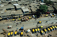 INDIEN Megacity Metropole Mumbai Bombay, Menschen leben in Huetten im Slum Dharavi, Taxis auf Strasse / INDIA Mumbai Bombay, Dharavi slum, huts of migrants and cabs at street