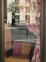 The reflected image of a small Parisian square, with its characteristic drinking fountain and a characteristic building on the background. Across the reflecting shop window there are a curtain and a sofa. A woman is entering into the square on the distance (Paris, 2007).<br /> <br /> L'immagina riflessa di una piccola piazza Parigina, con la sua tipica fontanella ed un palazzo tipico sullo sfondo. Attraverso la vetrata riflettente del negozio, si vedono una tenda e un sofà. In lontananza, una donna sta entrando nella piazza (Parigi, 2007).