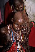 Lolgorian, Kenya. Siria Maasai; Eunoto ceremony; moran having his braided hair shaved off by a woman.