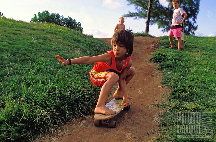 Young boy skateboarding down a dirt path