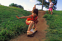 Young boy skateboarding down a dirt path