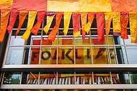 Colorful banners reflecting on glass window panels, Northwest Folklife Festival 2016, Seattle Center, Washington, USA.