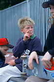 12 year old boy smoking a cigarette at a skateboard bowl in Camden, London.