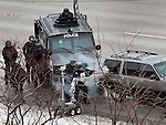 standoffp4, mjs, news - A tactical team stands behind their armored truck as two members of the team throw in what appears to be tear gas into the SUV, in Milwaukee on Friday, December 10, 2010. PHOTO BY MARK ABRAMSON/MABRAMSON@JOURNALSENTINEL.COM