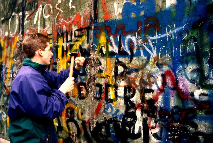 BERLINO / GERMANIA - 10 NOVEMBRE 1989.UN GIOVANE BERLINESE CERCA DI APRIRE UNA BRECCIA NEL MURO NELLA ZONA DELLA PORTA DI BRANDEBURGO..FOTO LIVIO SENIGALLIESI..BERLIN / GERMANY - 10 NOVEMBER 1989.YOUNG INHABITANT OF WEST BERLIN TAKING PIECES OF WALL NEAR BRANDEBURG TOWER..PHOTO BY LIVIO SENIGALLIESI