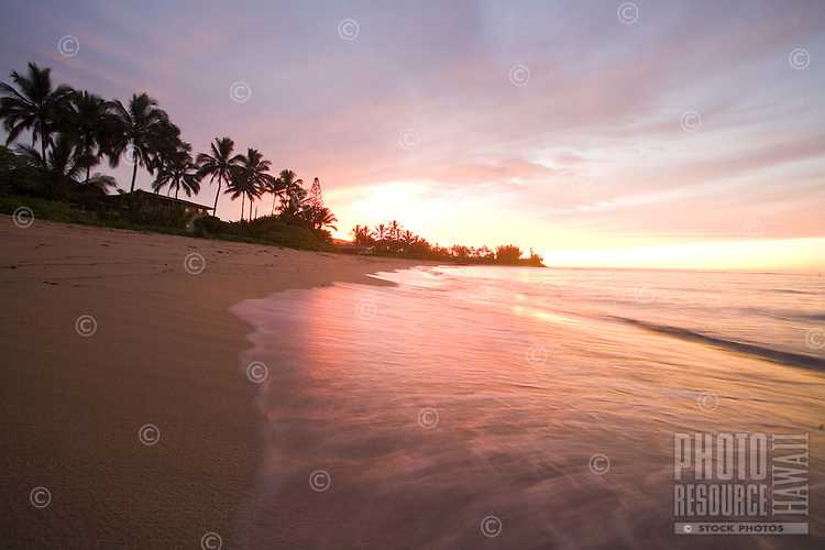 Sunset on Waialua Beach, with calm waves in foreground