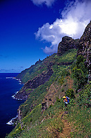 Hiker on the challenging Kalalau trail, Na Pali coast, north shore Kauai
