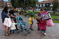 Peru, Cusco.  Vendors Offering Souvenirs to Family Visiting the Plaza de Armas.