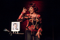 "The BKA Club in Berlin which has nightly politically satirical, sexy and comic revues. In this act a flame haired transvestite sings a song to the portrait of her ""Stasi Romeo"" (referring to the former East German secret police).."