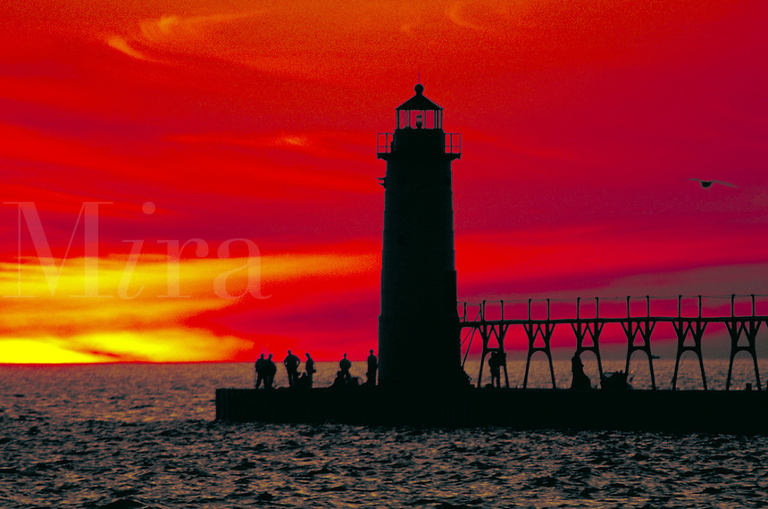 Sunset view of of Manistee North Pierhead Lighthouse and sport fishermen on pierhead. Manistee Michigan USA Lake Michigan.