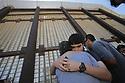 Monica Nieblas hugs her son Eduardo Rivas, 13, as his father, Cain Rivas, behind at right, looks through the border wall at Friendship Park, 04/16/17, in San Diego, California.  photo by Bill Wechter