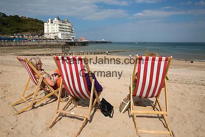 United Kingdom, Wales, Conwy, near Llandudno: deckchairs on beach with the Grand Hotel | Grossbritannien, Wales, Conwy, bei Llandudno: Liegestuehle am Strand, das Grand Hotel im Hintergrund