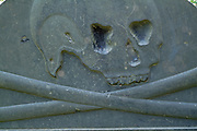Old weathered skull & crossbones headstone in a New England graveyard.