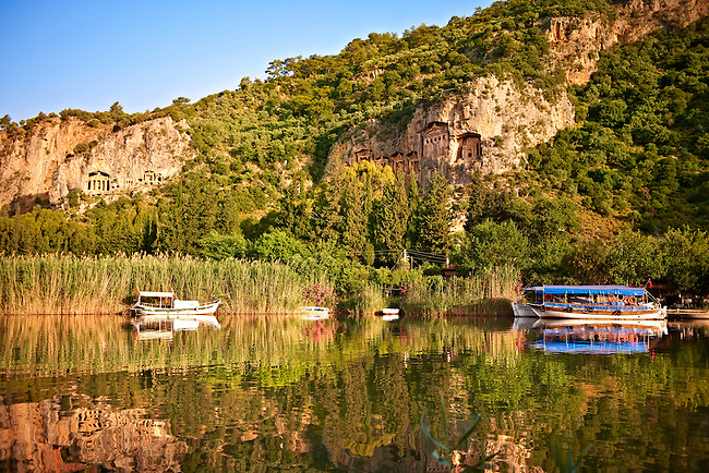 Boats on Dalyan Çay? River with Lycian Rock Tombs in the cliffs . Mediterranean coast Turkey