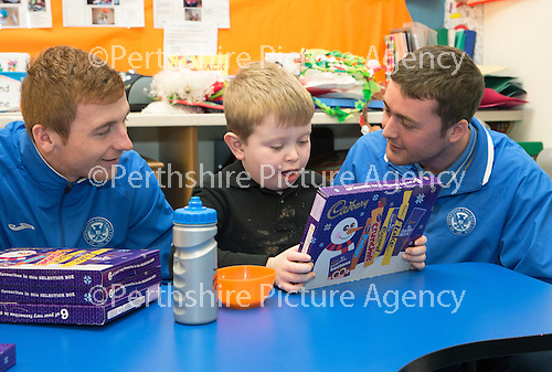 St Johnstone players visit Fairview School in Perth.....19.12.13<br /> Kevin Poynter gets a selection box from Liam Caddis and Tom Scobbie<br /> Picture by Graeme Hart.<br /> Copyright Perthshire Picture Agency<br /> Tel: 01738 623350  Mobile: 07990 594431