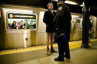 A participant in the 5th annual No Pants Subway Ride stands under police guard and without pants on the platform of the #6 line train in New York City, USA, 22 January 2006. The artists and pranksters of the Improv' Everywhere group organised the ride, which gathered over 150 participants, in order to surprise and amuse other passengers and themselves. The police issued summons and detained several participants.