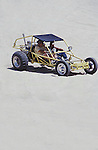 TWO MEN WATCH TOURIST IN ATV'S ON SAND DUNES