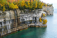 Fall colors and a narrow waterfall line the Pictured Rocks shoreline near Grand Portal Point.