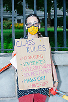 """A demonstrator holds a sign reading """"Class rules / no sharing, stay seated, no groupwork, six feet apart, masks on, have fun?"""" as people gathered outside the Massachusetts State House for a protest organized by the Massachusetts Teachers Association against current school reopening plans during the ongoing Coronavirus (COVID-19) global pandemic in Boston, Massachusetts, on Wed., Aug. 19, 2020. The teachers' union, alongside two other Massachusetts teachers' unions, organized the event as part of a mass day of action demanding that the school year starts with remote learning and switch to in-person learning only when health and safety standards can be guaranteed."""