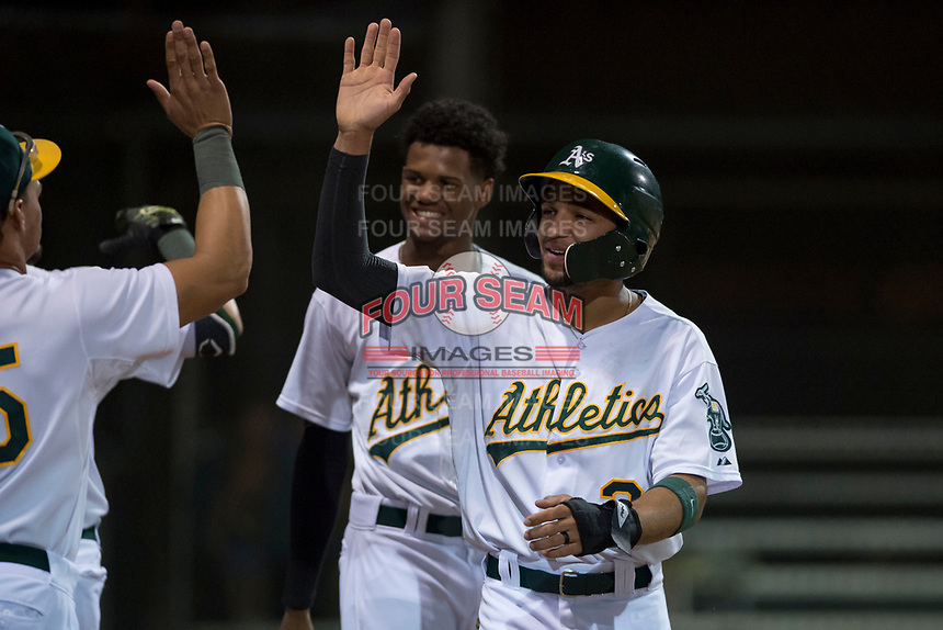 AZL Athletics shortstop Yerdel Vargas (2) is congratulated by teammates after scoring a run during an Arizona League game against the AZL Giants Orange at Lew Wolff Training Complex on June 25, 2018 in Mesa, Arizona. AZL Giants Orange defeated the AZL Athletics 7-5. (Zachary Lucy/Four Seam Images)