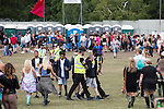 © Joel Goodman - 07973 332324 . 07/06/2015 . Manchester , UK . Security detain and remove a man at The Parklife 2015 music festival in Heaton Park , Manchester . Photo credit : Joel Goodman