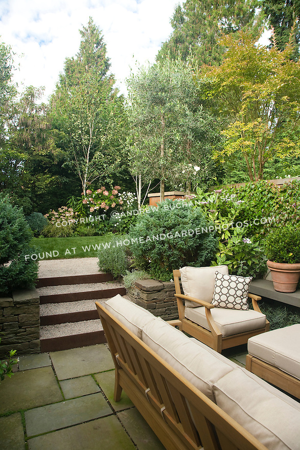 Stone steps connect the lower patio and middle lawn areas in this multi-level Seattle backyard.