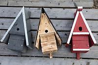 Selbstgebaute Holz-Nistkästen, Nistkasten für Vögel aus Holz, Vogelkasten, Meisenkasten selber bauen, selbst bauen, Basteln, Bastelei selbst bauen, selbermachen, selbstmachen. 3 fertige Nistkästen mit unterschiedlichen Einfluglöchern, Einflugloch: links (grau) für Blaumeise mit kleinem Loch. mitte (Holz geflämmt) mit größerem Loch für Kohlmeise, Trauerschnäpper, Spatzen. rechts (rot) mit hochovalem Einflugloch für Gartenrotschwanz