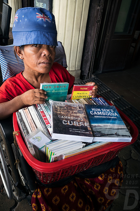 A handicapped and disabled women in a wheelchair selling books in the streets of Phnom Penh, Cambodia