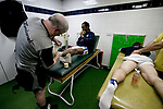 Tranmere Rovers 2  Port Vale 0, 20/03/2019. Prenton Park, League One. Club physiotherapist Les Parry applying tape to team captain Ian Goddison's ankle in the dressing room at Prenton Park, home of Tranmere Rovers, as his team prepare to face Port Vale in a English League One fixture. Les Parry has been the club physiotherapist since 1993 and recently completed 800 games with the club. At the time he was also working on completing his PhD at Liverpool John Moores University. Photo by Colin McPherson.
