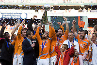 Houston Dynamo captain (24) Wade Barrett raises the trophy as the rest of the team celebrates after the MLS Cup Finals at RFK Stadium in Washington, DC.  The Houston Dynamo defeated the New England Revolution, 2-1, to win the Alan I. Rothenberg Trophy.