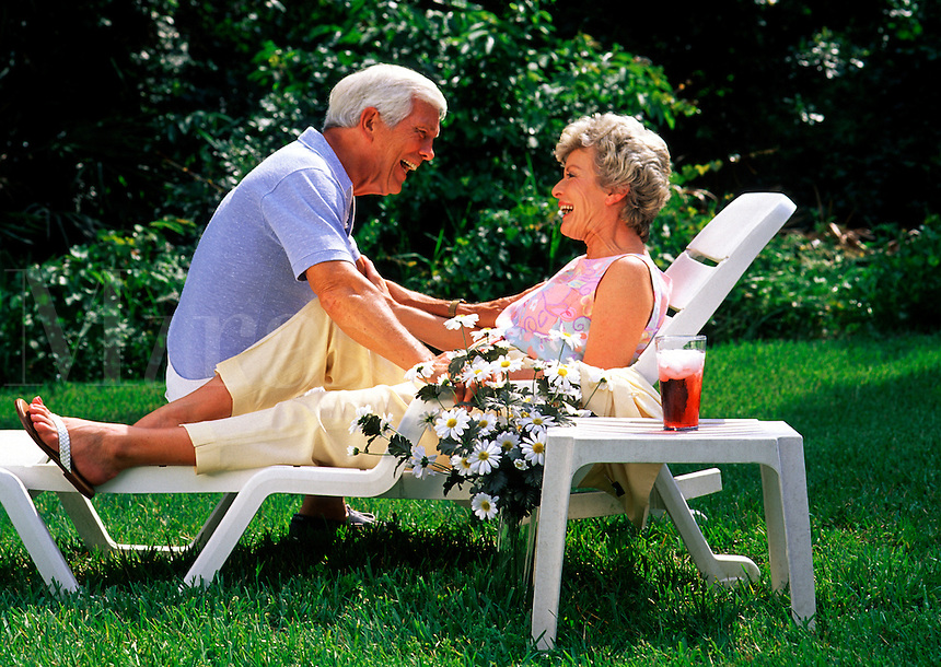 portrait of a smiling senior couple as they talk and laugh as they relax outside.