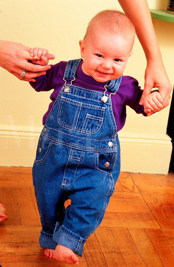 Infant learns to walk with his mothers help